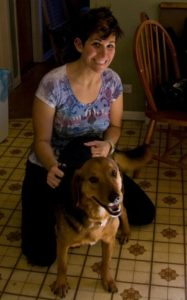 a young Steph Haddad in 2010, kneeling with a floppy-eared beagle german shepherd mix wagging his tail.
