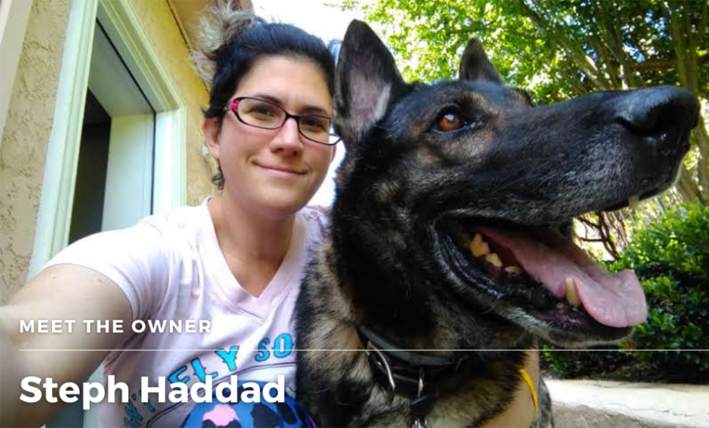 Selfie photo of Steph, a white woman with pink rimmed glasses, next to the large head of a German bred German shepherd with his tongue hanging out.